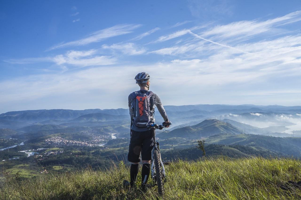 Cyklist blickar ut över landskap.